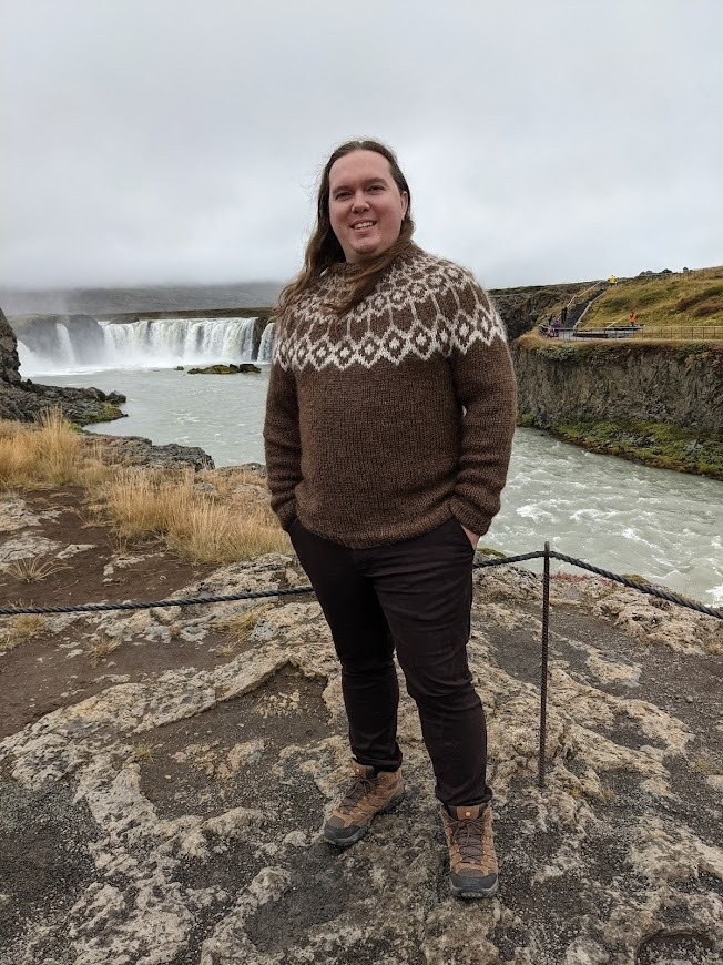 Sean, in a sweater, standing in front of the Goðafoss waterfall in northern Iceland.